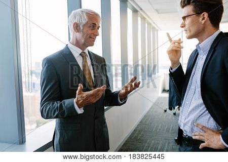 Indoor shot of senior manager discussing work with a colleague. Two businessmen talking in office.