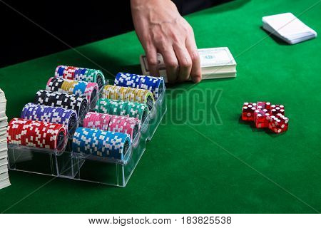 A hand putting stack of dollar for betting with a card on green table and has chips in box placed near red dice