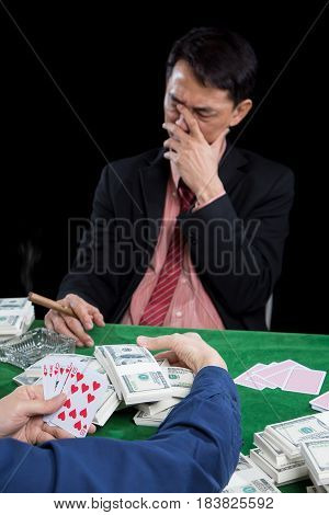 Selective focus at contender gathered a pile of bet and show winner to opponent in a poker game The blurry gambler used hand off the face with stressed on black background casino concept