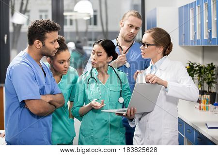 Group Of Medical Workers Using Laptop During Discussion In Lab
