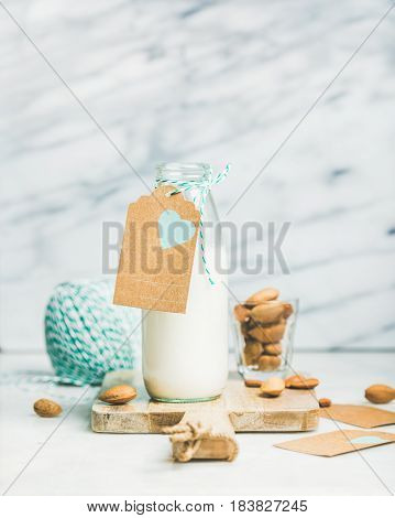 Fresh vegan dairy-free almond milk in glass bottle with craft paper label with copy space and blue rope, grey marble background. Vegan, vegetarian, raw, healthy, clean eating, diet, detox food concept