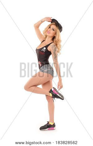 Beautiful sexy tattooed girl in studio isolated. Dressed in black swimsuit with embroidered