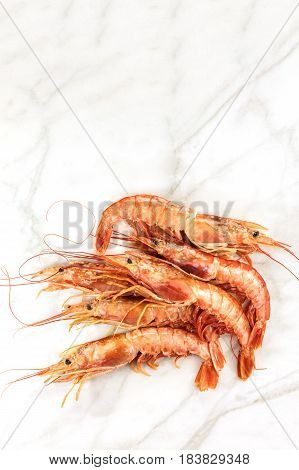 Raw shrimps, shot from above on a white marble table with a place for text
