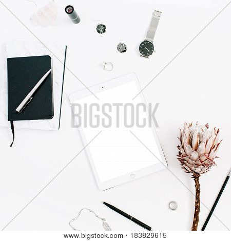 Blogger or freelancer workspace with blank screen tablet protea flower notebook watches and feminine accessories on white background. Flat lay top view minimalistic decorated home office desk.