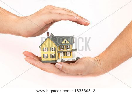 Women's Hands Holding and Protecting a Model of a House