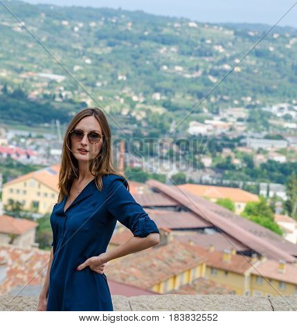 Young woman tourist wearing shades admiring the view from a high spot of city Grasse in France