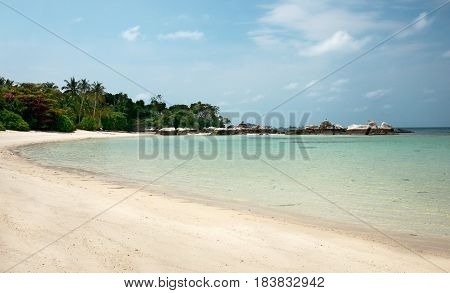 Stretched out white sand beach with natural rock formation at the coastline on the horizon in Belitung Island in the afternoon Indonesia.