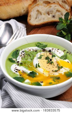 Pea puree soup with poached egg sour cream mint leaves seasoned with spices.