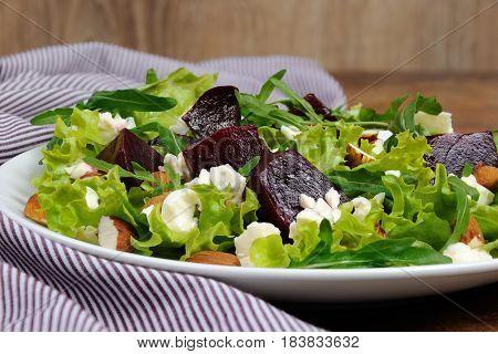 Salad vinaigrette with beets lettuce arugula feta and almonds