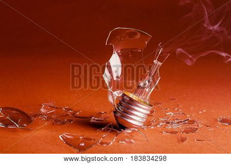 Burned Standard Incandescent Bulb with Smoke on Red Background
