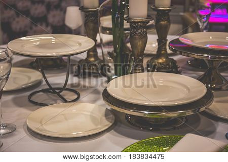 Served table in the restaurant, plates, candlesticks, close-up, toned photo