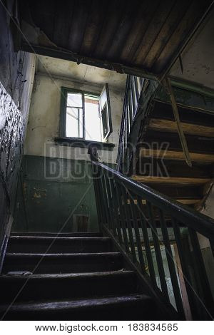 Dark grim wooden stairs in old abandoned building or factory. Old Stairs, dirty walls and open window. Vertical image