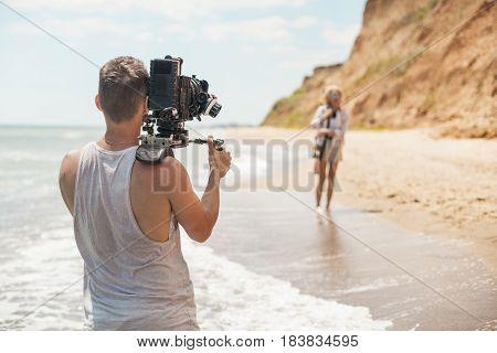 Videographer shoots clip for famous star on the sand beach near sea or ocean