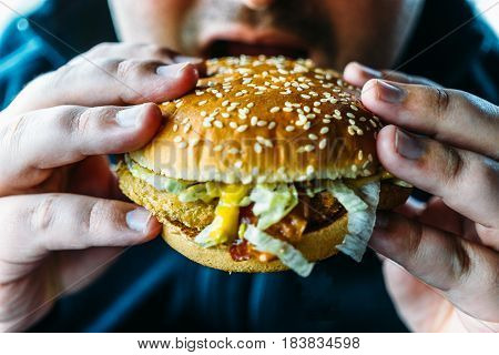 Hungry fat man holds hamburger and going to bite fas food. Unhealthy food concept