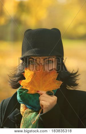 Portrait of young beautiful trendy woman standing on nature autumn background and smiling