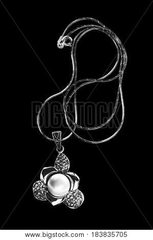 Pendant with pearl and diamonds on a chain on black background