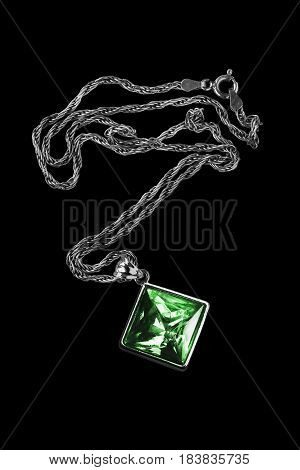 Green crystals pendant on silver chain on black background