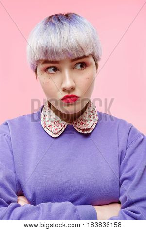 Fashion close-up portrait of angry beautiful dollish girl with short light violet hair wearing lilac sweater over pink background. Copy space.