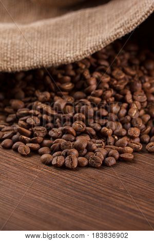 Coffee Is Poured From A Burlap On A Wooden Background