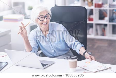 Look at me. Happy smiling female holding pencil in right hand putting her left hand on the folder while looking straight at camera