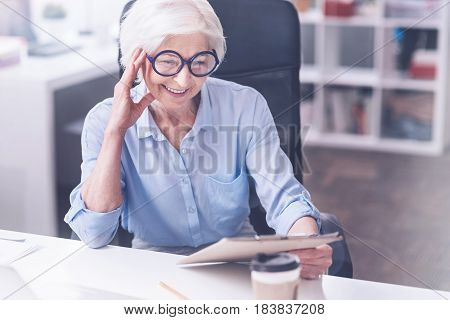Feeling happiness. Delighted pensioner worker leaning on her right hand looking attentively at folder while sitting on big chair