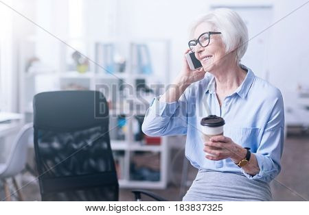 Time for coffee. Positive delighted female sitting on the table holding telephone in right hand while looking sideways