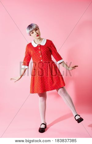 Picture of beautiful dollish girl with short light violet hair wearing red dress over pink background. Copy space.