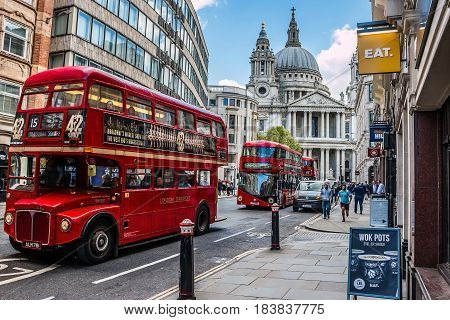 London, UK - April 25 2017: Busy street in central London with classic retro and new modern double decker buses and St. Paul's Cathedral in the background. HDR style image