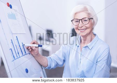 I am ready. Delighted female wearing glasses keeping smile on her face while doing diagram on the board
