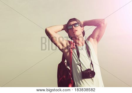 Handsome man caucasian photographer or traveler with muscular hands biceps triceps in stylish sunglasses and cap camera red backpack enjoy sunlight on sunny grey sky. Leisure and summer vacation