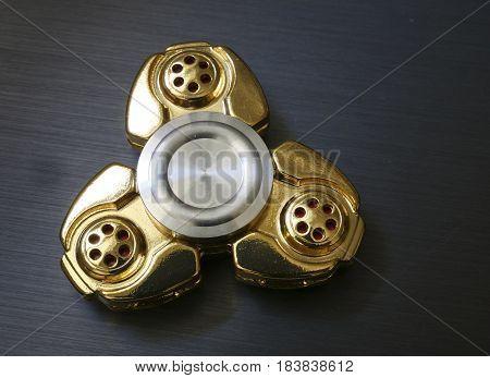 Golden Fidget Spinner Toy On Dark Aurface