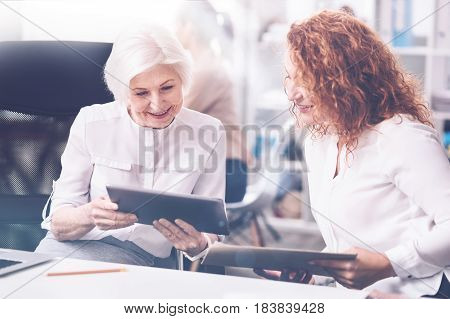 Nice idea. Pretty woman keeping smile on her face, holding device in both hands while showing it to her colleague