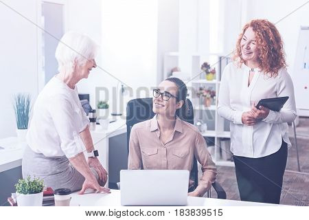 Good day. Elderly businesswoman sitting in semi position putting her right hand on the table while looking at her assistants