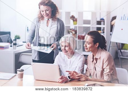 Be confident. Smiling elderly female working together with younger colleagues touching her computer while sitting between them
