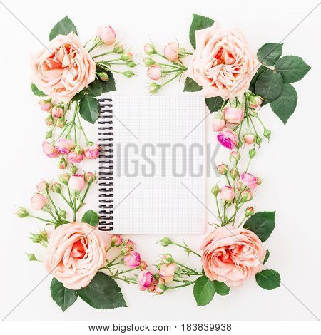Floral frame with pink flowers, buds, branches, leaves and paper notebook on white background. Flat lay, Top view.