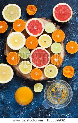 Fresh juice and citrus fruits: oranges lemons grapefruits and limes on the round wooden board on the dark blue background top view