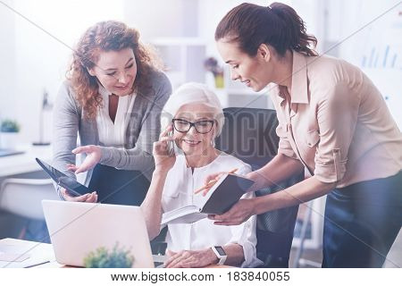 Your offers. Happy female in stylish glasses keeping smile on her face while listening to her interlocutor, looking at the screen of her computer