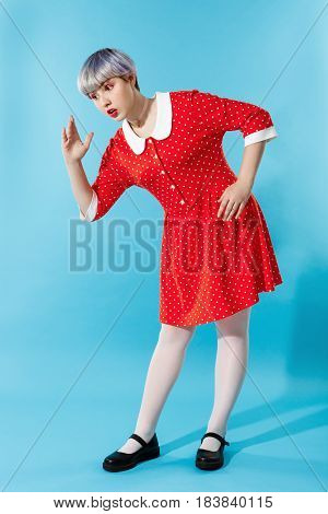 Picture of beautiful dollish girl with short light violet hair wearing red dress over blue background. Copy space.