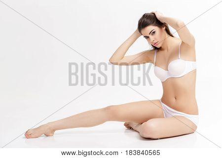 young beautiful brunette woman with long slender legs in white underwear. sitting on floor on white background