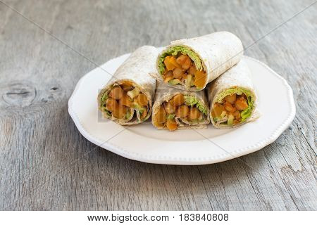 Four vegetarian tortillas with chickpeas butternut squash spring onion cucumber avocado on the dark wooden table copy space for text