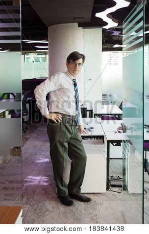 Handsome man in shirt and tie poses in modern office with tables