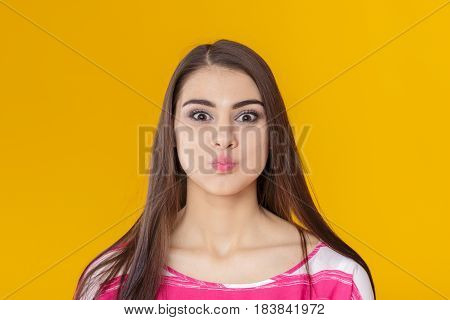 funny young brunette woman fooling around on a yellow background.