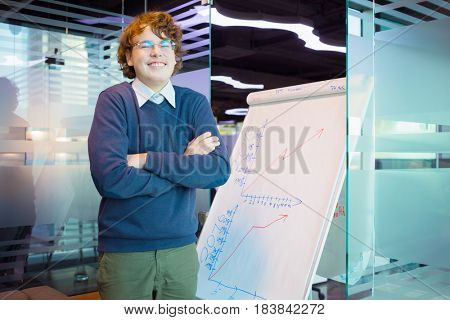 Funny teenager in glasses stands near graphs on paper in modern office