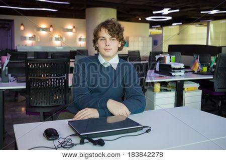 Handsome serious teenager sits at table with laptop in modern office with many workplaces