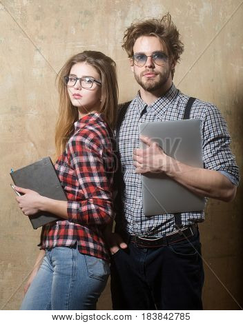 nerd couple of students in geek glasses. Pretty girl or beautiful woman with notebook and handsome man with laptop computer in checkered shirts on beige background. Education and technology