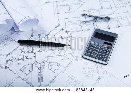 Blueprints with glasses, drafting writing utensil and calculator