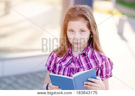 Ten Years Old Blue Eyed Schoolgirl Reading A Book