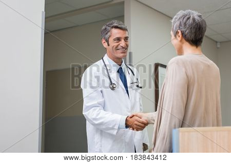 Mature male doctor and senior woman patient shaking hands at hospital. Happy doctor shaking hands with old woman for her healing in hospital. Smiling doctor greeting patient at clinic reception desk.