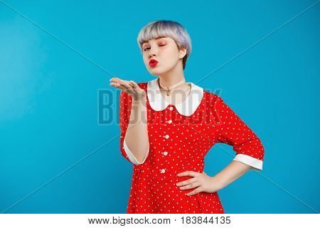 Close up portrait beautiful dollish girl with short light violet hair wearing red dress sending kiss over blue background. Copy space.