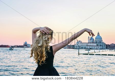 Portrait of a woman looking at the Santa Maria della Salute church in Venice. Blonde Girl wearing a black mask admiring the view at Grand Canal, Italy. Sunset dreaming illusion